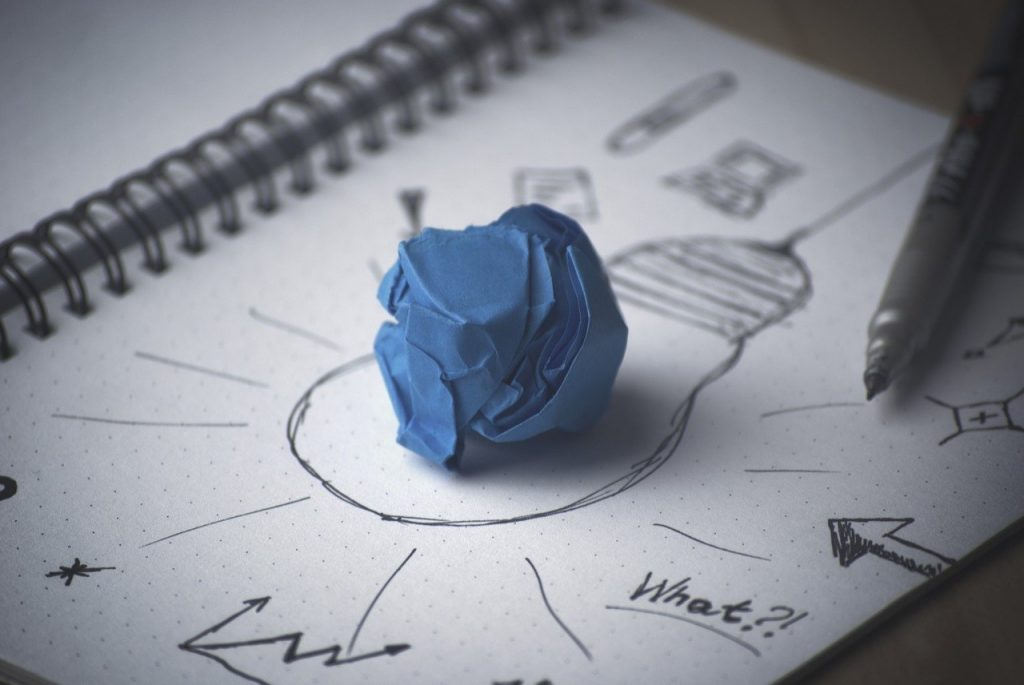 Web design ideas theme graphic: drawing of lightbulb with wadded blue paper ball in the center and idea map surrounding