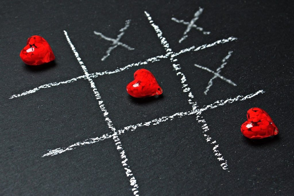 Tic tac toe drawn in chalk with hearts forming a winning diagonal