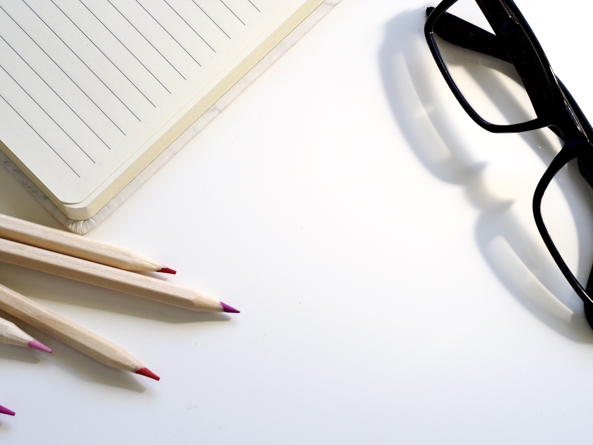 Paper, pencils, and a pair of glasses (symbolizing content writing)